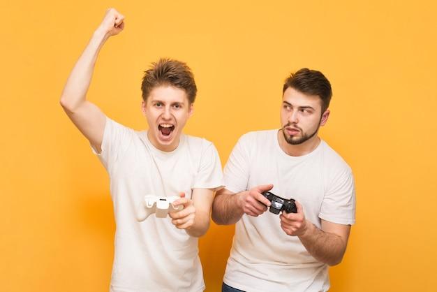 Spieler in weißen t-shirts halten den joystick in den händen und spielen emotional videospiele, isoliert auf gelb