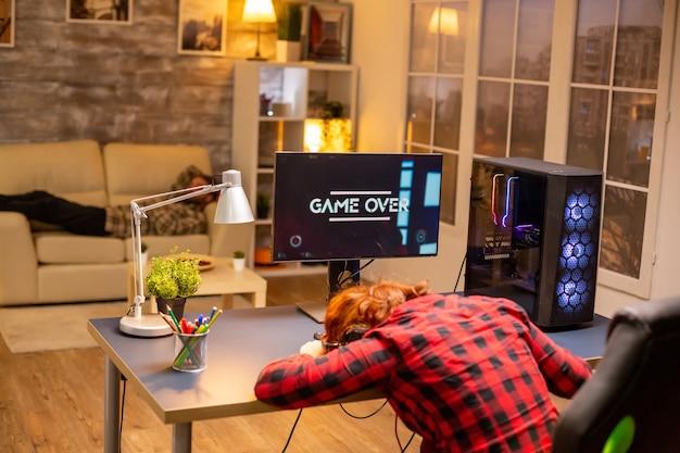 Spielerfrau, die bei einem videospiel verliert, das spät nachts im wohnzimmer spielt.
