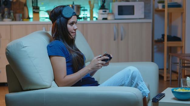 Spielerfrau, die videospiele auf der konsole mit controller und joysticks spielt, die auf der couch vor dem fernseher sitzen. aufgeregte entschlossene person, die das spielen mit dem drahtlosen controller entspannt, der spaß beim gewinnen hat