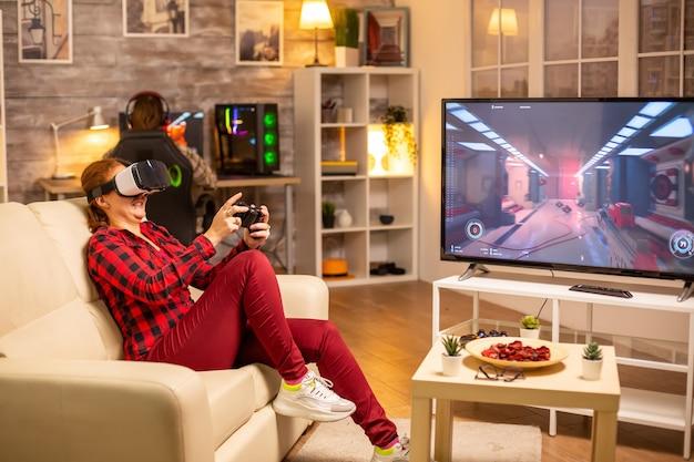 Spielerin, die spät nachts im wohnzimmer videospiele mit einem vr-headset spielt