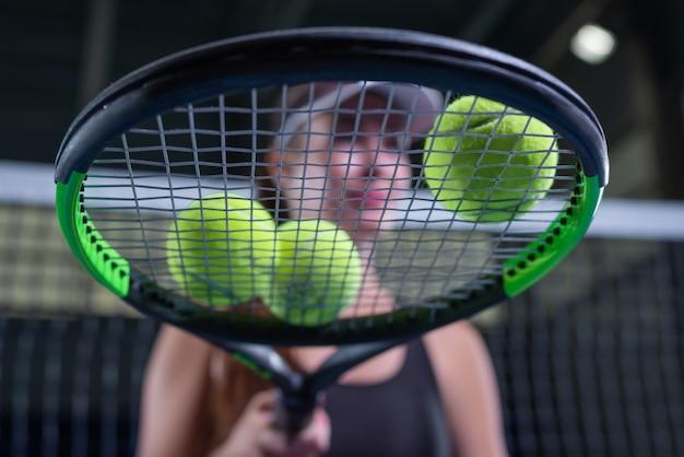 Spielerin mit tennisschläger und bällen, die am netz sitzen