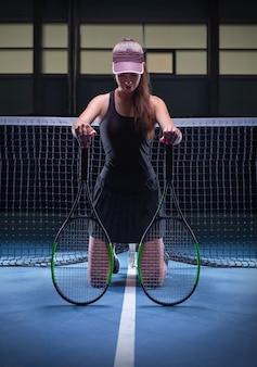Spielerin mit tennisschlägern am netz sitzend