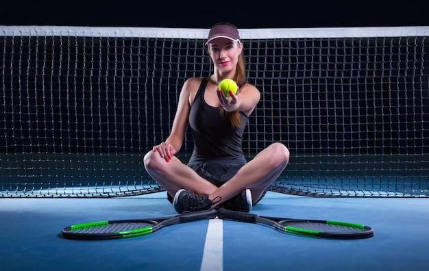 Spielerin mit tennisschlägern und ball sitzt am netz