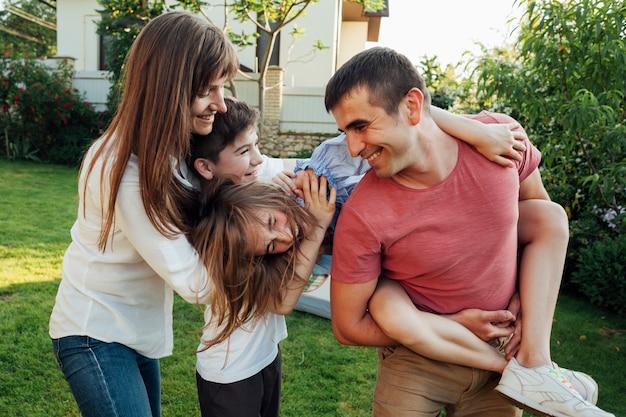 Spielerische familie, die spaß zusammen am park hat
