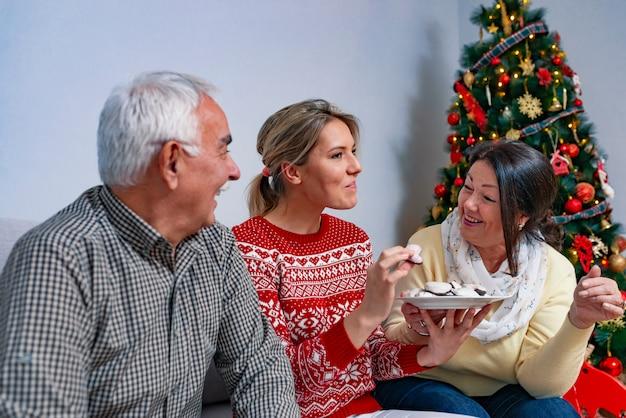Spielerische familie, die zu hause lebkuchenplätzchen isst.