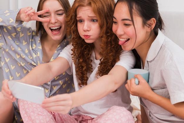 Spielerische gruppe freundinnen, die pyjama-party haben