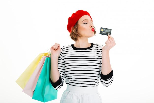 Spielerische ingwerfrau, die pakete hält und mit kreditkarte über grau spielt