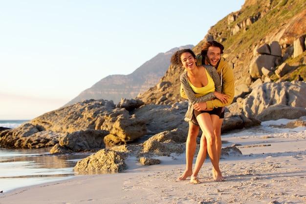 Spielerische junge mischrassepaare am strand