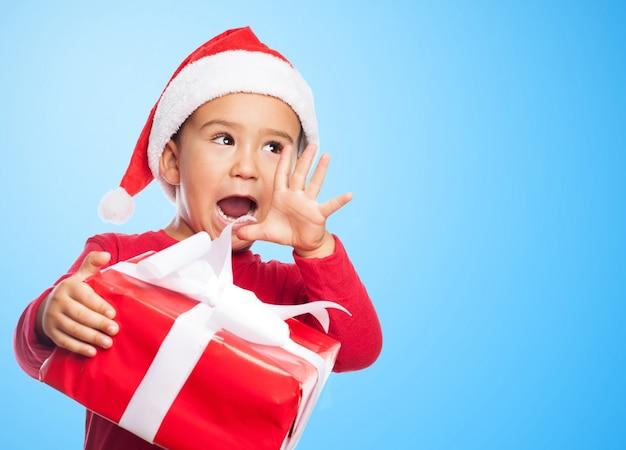Spielerische junge schrie, während ein geschenk hält