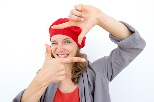 Spielerische kreative geschäftsfrau konzentriert sich auf projekt. fröhliche junge französische frau schaut durch die hände und zwinkert. business-konzept-konzept