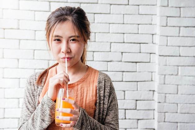 Spielerische und reizende asiatische frau, die im gemütlichen haus sich entspannt und orangensaft trinkt