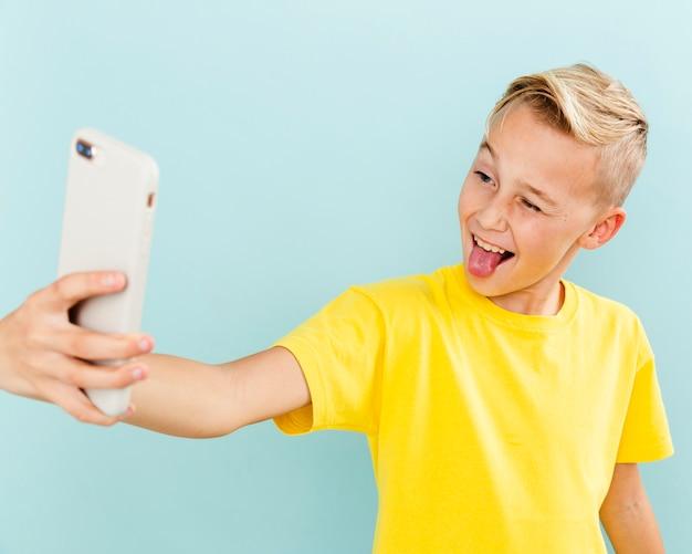 Spielerischer junge der vorderansicht, der selfie nimmt