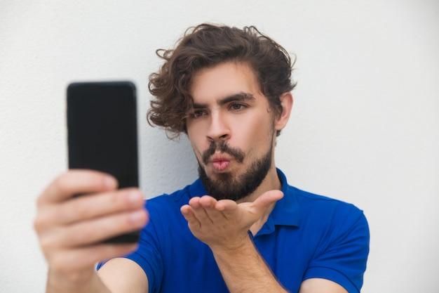 Spielerischer positiver kerl, der selfie auf smartphone nimmt