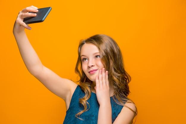 Spielerisches glückliches jugendlich mädchen mit telefon