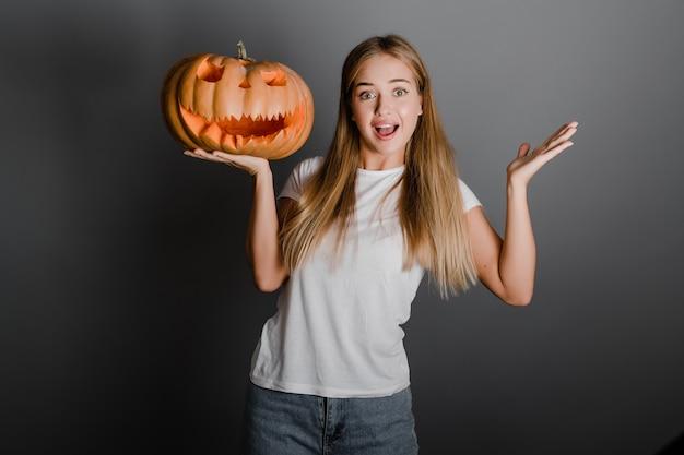 Spielerisches lustiges blondes mädchen mit dem halloween-steckfassung o-laternenkürbis getrennt über grau