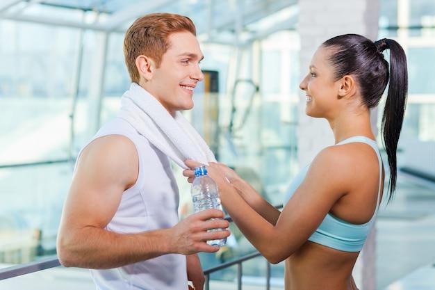 Spielerisches paar im fitnessstudio. schöne junge sportliche paare, die beim stehen in der turnhalle sprechen und lächeln