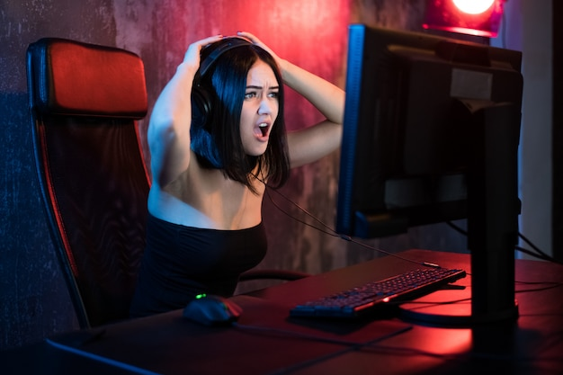Spielermädchen. aufgeregte wütende schockierte junge frau, die videospiele auf einem pc-computer schreiend spielt