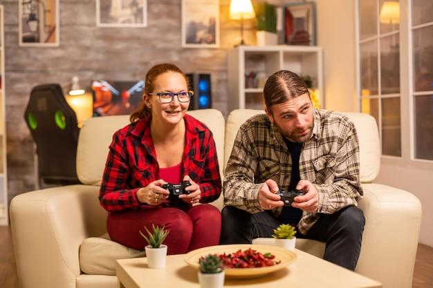 Spielerpaare spielen videospiele auf dem fernseher mit drahtlosen controllern in den händen.