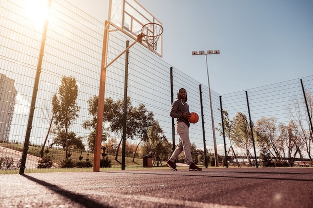 Spielgebiet. positiver freudiger mann, der einen ball hält, während er im basketballplatz geht
