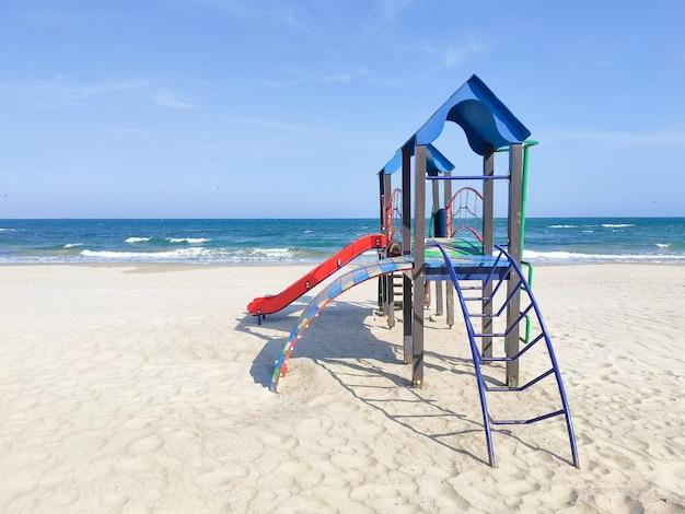 Spielhaus für kinder im sand am meer. spielplatz am strand, sonniger tag, niemand. konzept der erholung, kinderaktivität, putdoor-unterhaltung.
