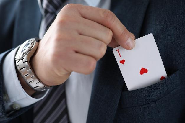 Spielkarte des männlichen geschäftsmannhandgriffs in der hand