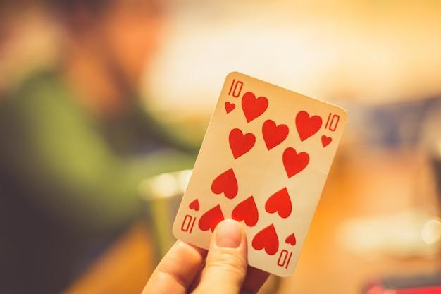 Spielkarte in den händen einer frau