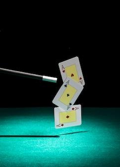 Spielkarte mit drei assen in der luft getan mit magischem stab über dem grünen hintergrund