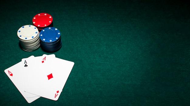 Spielkarte mit drei assen und stapel kasinochips auf grüner pokertabelle