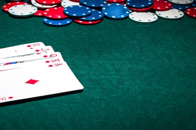 Spielkarte und kasinochips des royal flush auf grünem pokerhintergrund