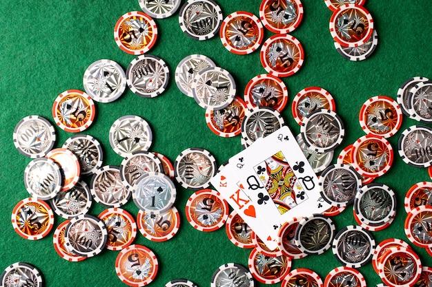 Spielkarten dame und könig und chips auf grünem hintergrund