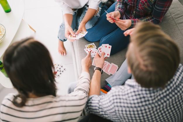 Spielkarten der kühlenden leute auf sofa