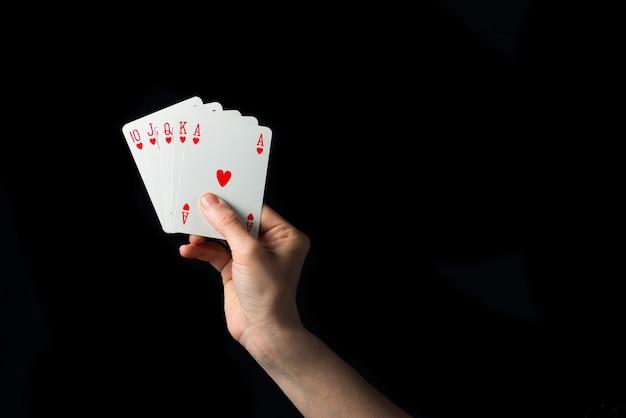 Spielkarten in der hand lokalisiert auf schwarzem hintergrund