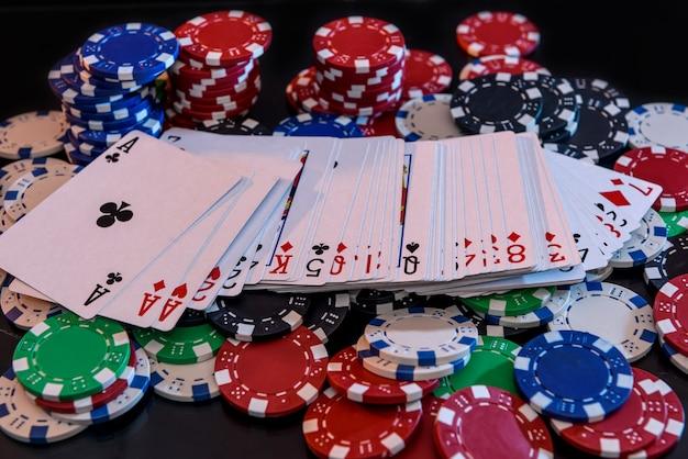 Spielkarten mit pokerchips auf schwarzem hintergrund