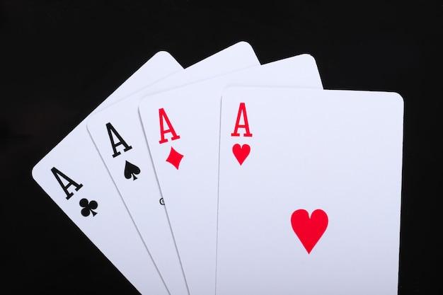 Spielkarten mit vier assen auf schwarz