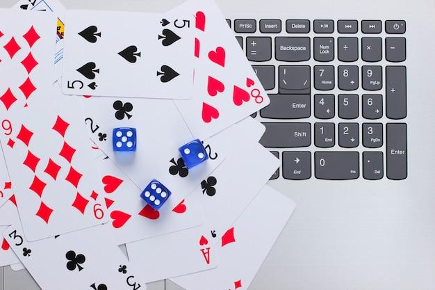 Spielkarten und blaue würfel auf einer laptoptastatur. online poker casino