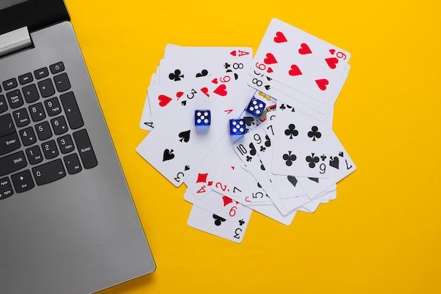 Spielkarten und blaue würfel, laptop-tastatur auf gelber oberfläche. online poker casino. draufsicht
