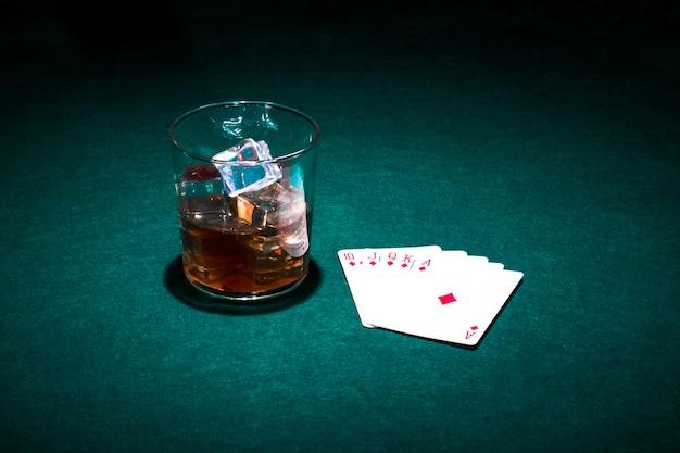 Spielkarten und glas whisky auf grüner tabelle