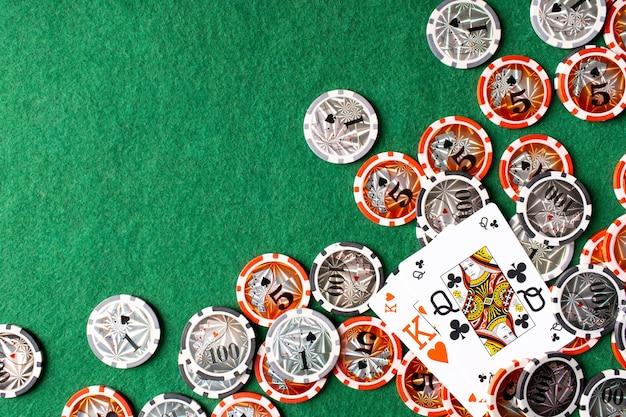 Spielkarten 'vier einer art' und chips auf grünem hintergrund