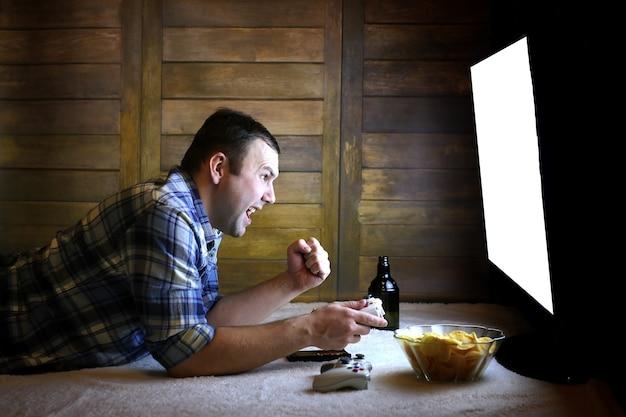 Spielmann, der auf einer konsole auf dem joystick vor dem großen fernsehbildschirm spielt