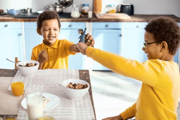 Spielpartner. angenehme kleine jungen, die am küchentisch sitzen und während des frühstücks spielerisch mit spielzeugdinosauriern kämpfen