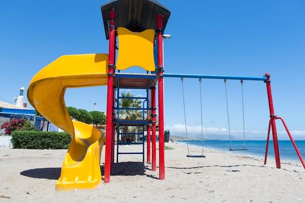 Spielstruktur für kinder mit rutschenschaukeln und kletterbereich am ufer am strand