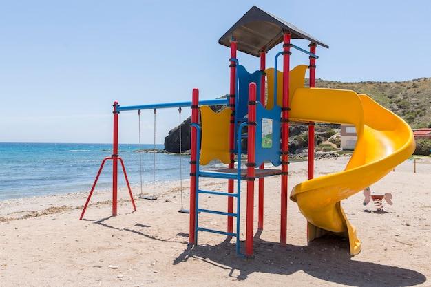Spielstruktur für kinder mit rutschenschaukeln und kletterbereich am ufer des spanischen strandes von puntas de calnegre
