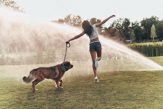Spielt nur mit ihrem hund. rückansicht der schönen jungen frau in voller länge, die mit ihrem hund beim laufen im freien spielt