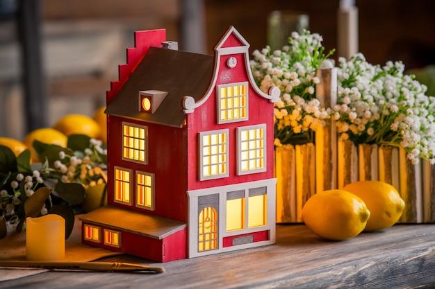Spielzeug dekorative lampe haus steht auf einem holztisch zwischen frühlingsblumen und innenelementen.