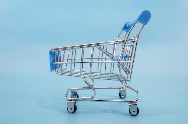 Spielzeug einkaufswagen auf einer blauen oberfläche