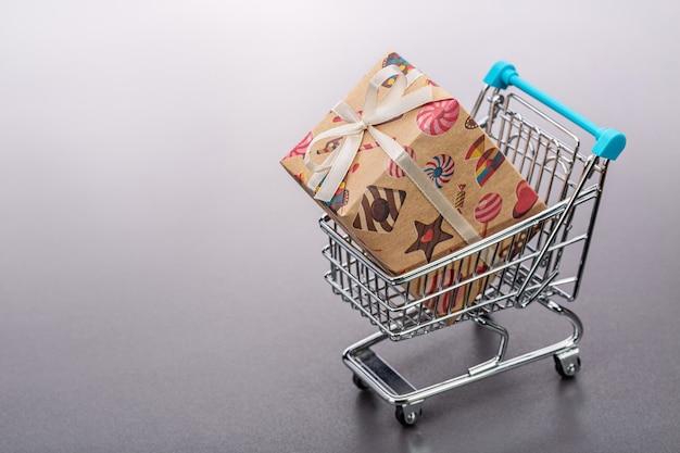 Spielzeug-einkaufswagen mit geschenk in der großen farbbox.