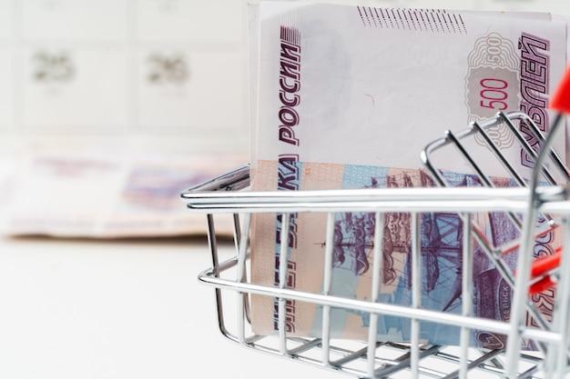 Spielzeug-einkaufswagen mit russischem rubelgeld. existenzminimum und kaufkraftkonzept