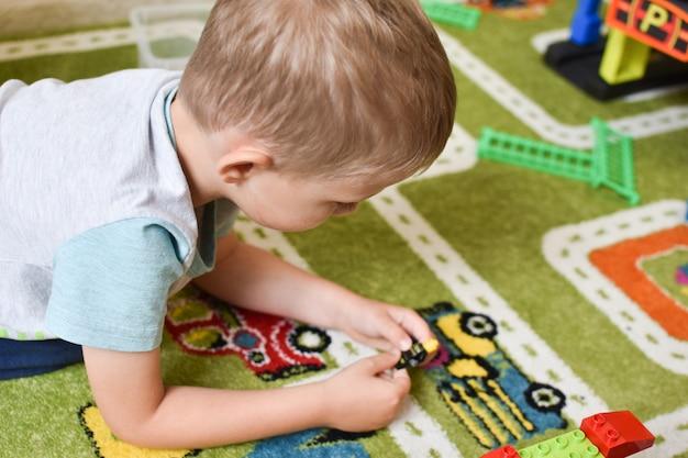 Spielzeug für jungen. kind mit einem zug auf dem boden