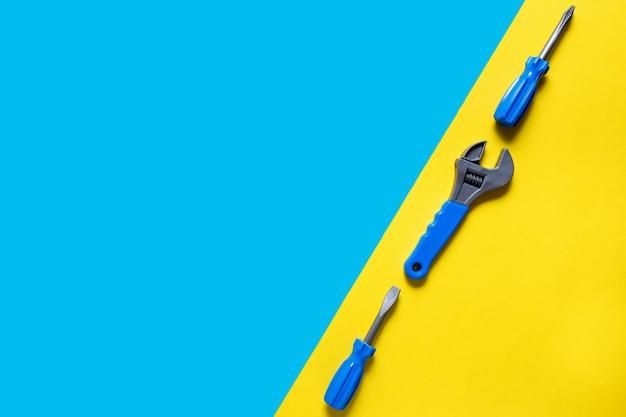 Spielzeug hintergrund. draufsicht der spielzeugwerkzeuge auf blauem gelbem hintergrund mit kopienraum für text.