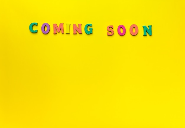 Spielzeug holzbuchstaben, die coming soon mit gelbem hintergrund buchstabieren